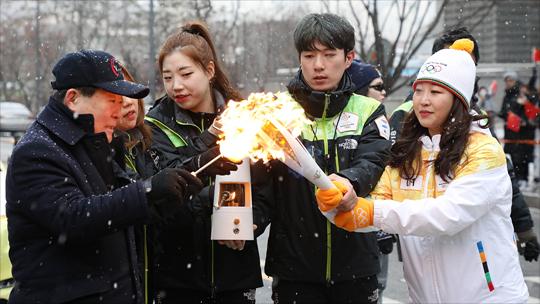 평창 동계올림픽 성화가 서울에 도착한 13일 서울 마포구 디지털미디어시티에서 서울지역 첫번째 성화봉송 주자가 박홍섭 마포구청장으로부터 성화를 전달 받고 있다. ⓒ데일리안 홍금표 기자