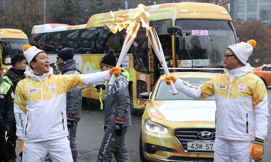 평창 동계올림픽 성화가 서울에 도착한 13일 서울 마포구 디지털미디어시티 일대에서 앞선 성화봉송 주자가 다음 주자에게 성화를 전달하고 있다. ⓒ데일리안 홍금표 기자