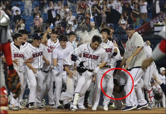 두산 김재환이 끝내기 투런 홈런 후 동료들의 환호를 받고 있다. 뒤에 머리를 쥐고 고통스러워하는 박건우의 모습이 보인다. ⓒ 연합뉴스