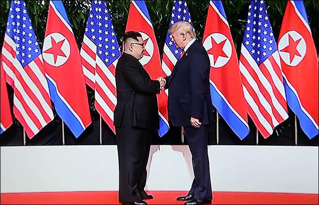 도널드 트럼프 미국 대통령과 김정은 북한 국무위원장이 12일 싱가포르 카펠라 호텔에서 역사적인 첫 북미정상회담에 앞서 악수를 하고 있다./jtbc 화면촬영 ⓒ데일리안