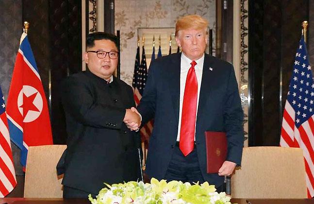 """지난 12일 싱가포르에서 열린 북미정상회담에서 김정은 북한 국무위원장과 도널드 트럼프 미국 대통령의 공동성명 서명식 모습. 이날 트럼프 대통령은 단독 기자회견에서 """"북한과 협상을 진행하는 동안 한미합동군사훈련을 중단하겠다""""고 언급한 바 있다. ⓒ연합뉴스"""
