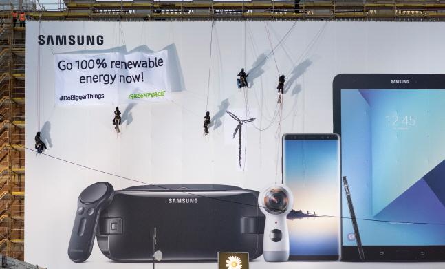 국제환경단체 그린피스가 삼성전자의 재생에너지 사용 확대 선언에 대해 환영 입장을 나타냈다. 사진은 그린피스 활동가들이 지난 1월 독일 베를린궁에 설치된 삼성전자 옥외광고판에 대형 현수막을 펼치며 삼성전자에 100% 재생가능에너지 사용 약속을 촉구하는 메시지를 전하고 있는 모습.ⓒ그린피스