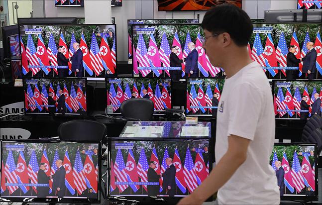 북미정상회담이 열린 12일 오전 서울 용산구 전자랜드에서 김정은 북한 국무위원장과 도널드 트럼프 미국 대통령의 북미정상회담이 텔레비전으로 중계되고 있다. ⓒ데일리안 홍금표 기자