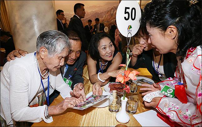 제21차 이산가족 상봉행사 첫날인 20일 오후 북한 금강산호텔에서 진행된 단체상봉에서 이금섬(92) 할머니가 아들 리상철(71)씨와 사진을 보고 있다. ⓒ사진공동취재단