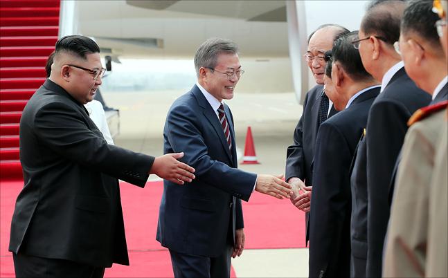문재인 대통령이 18일 오전 평양 순안공항에 도착해 김정은 북한 국무위원장이 지켜보는 가운데 북측 고위급 인사들과 악수하고 있다. ⓒ평양사진공동취재단